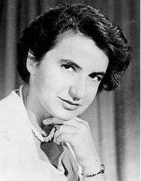 Portrait of Rosalind Franklin; a woman with short, dark hair which frames her face is smiling at the camera. Her right hand rests under her chin, a wristwatch visible, and what appears to be a pearl necklace around her neck.