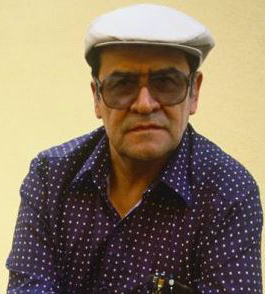 Portrait photo of Jaime Escalante; An older man in a white hat and large glasses looks directly into the camera with a look of determination. He's wearing a dark blue button-down shirt with rows of tiny white polkadots. What appear to be a few pens and a notebook, poke out the top of his left shirt pocket.