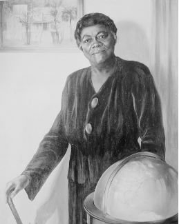 Mary McLeod Bethune photo; A mature woman in a long, dark dress standing behind a globe. She holds a cane in her left hand.
