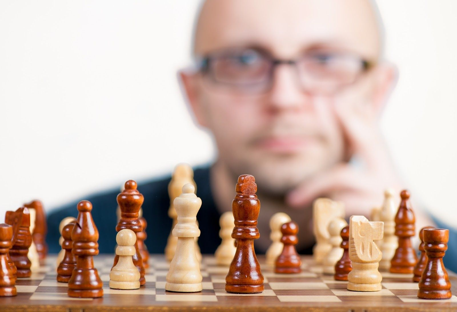 Man staring at chessboard considering next move