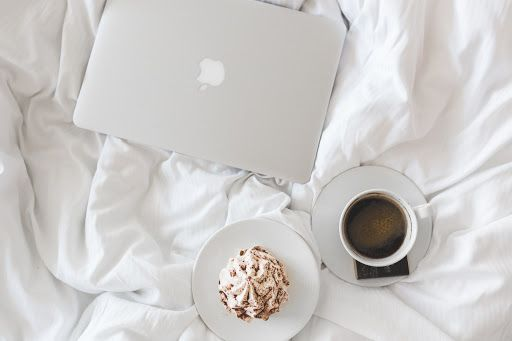 laptop, coffee cup, and a pastry on a bed