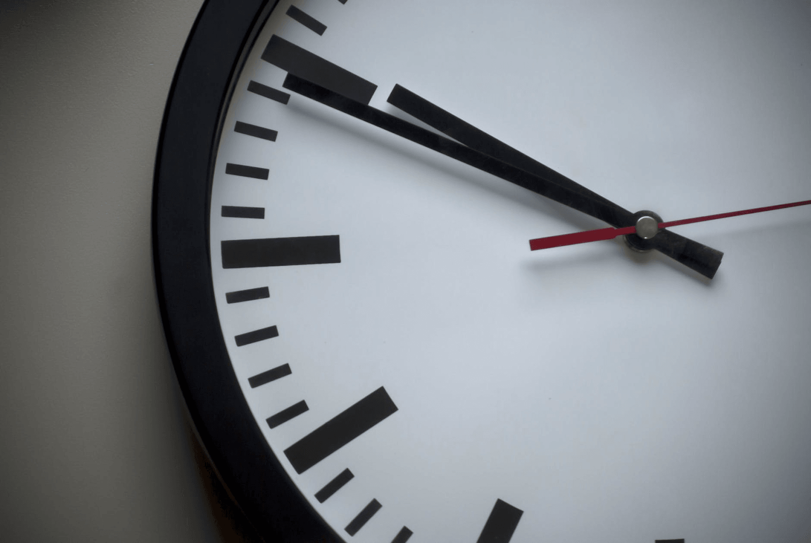 A black and white analog clock with a red seconds hand.