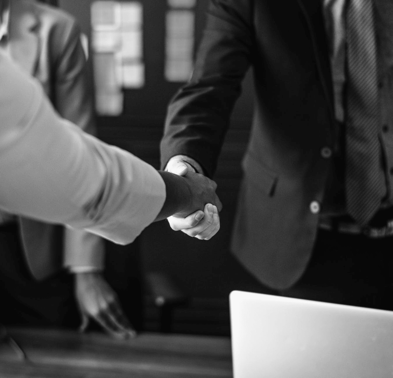 Black and white photo of two people shaking hands.