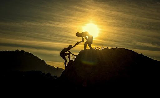 friends help each other up a mountain