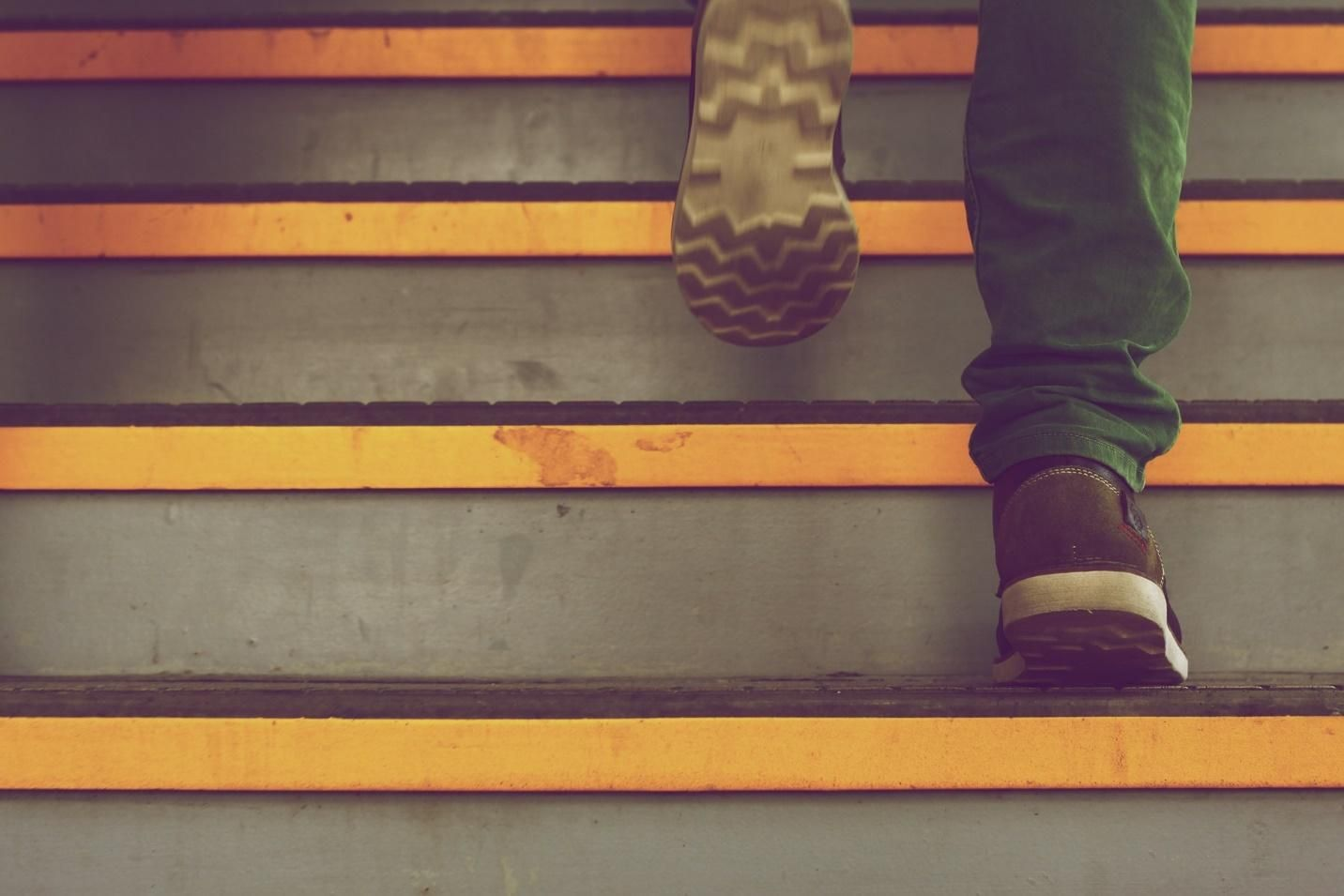 person walking up steps as part of a process