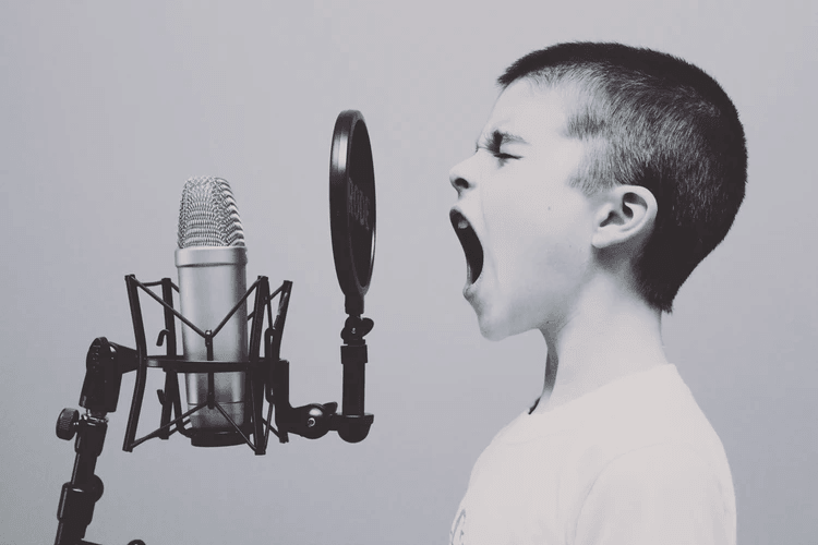 A young boy singing into a microphone.