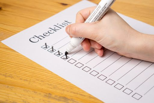 Black marker checking new hire onboarding checklist