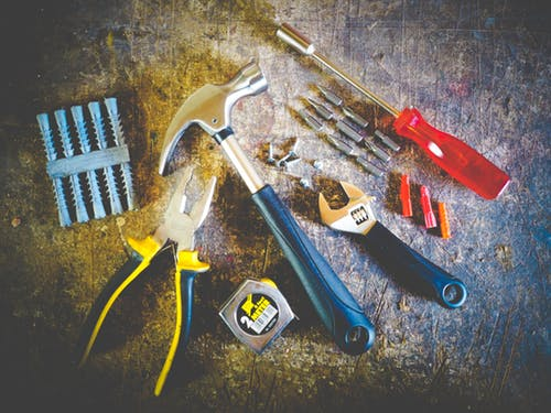 A pile of tools including a hammer, tape measure, and wrench.