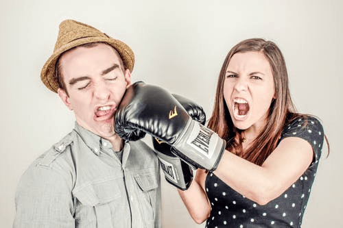 A woman with boxing gloves punching a man in the face.