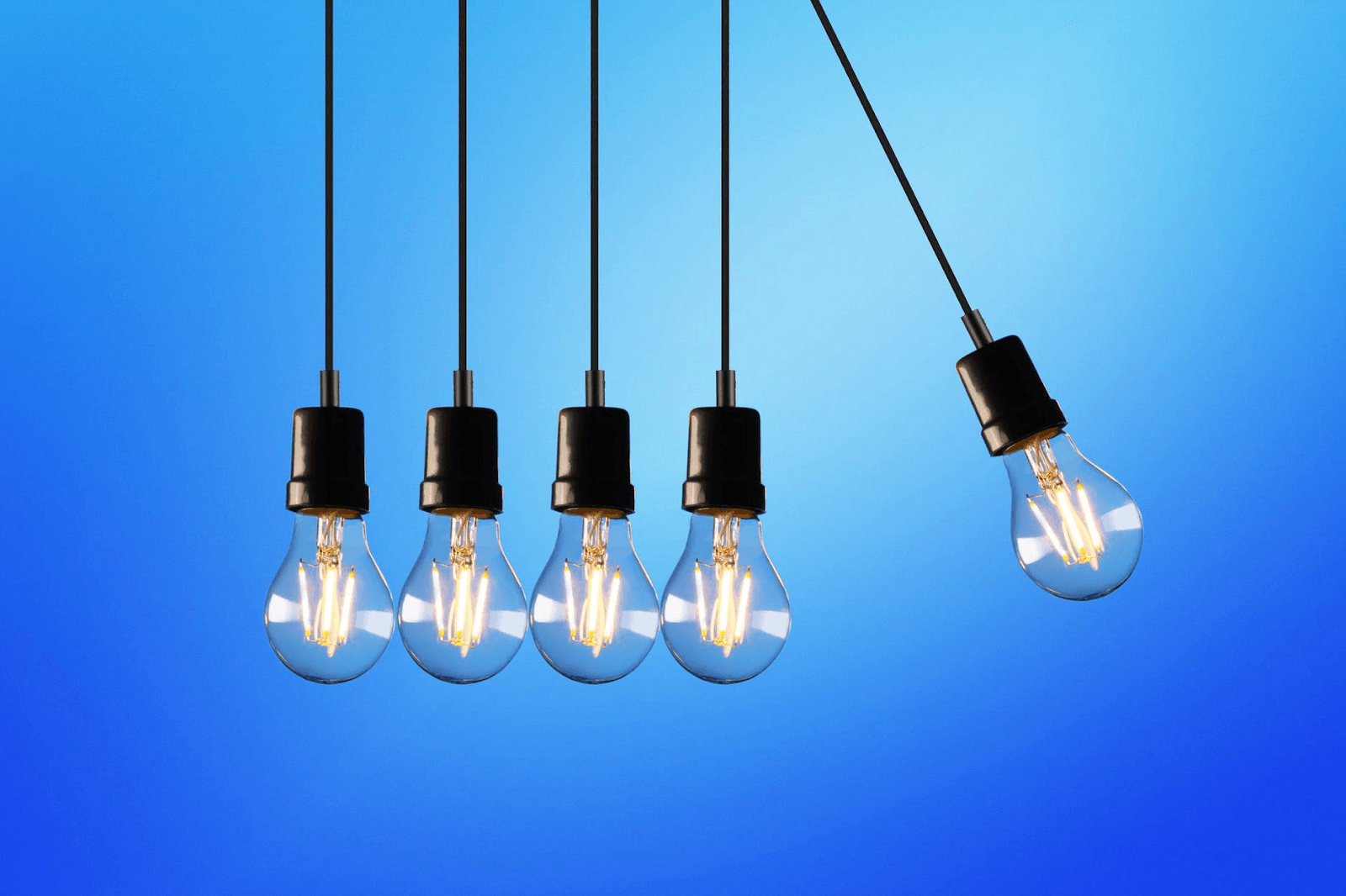 Five hanging light bulbs with a blue background.