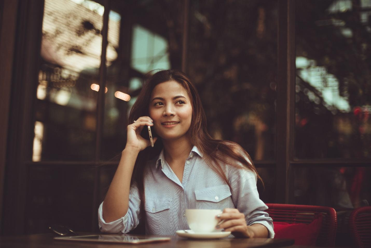 woman takes a business call at a cafe