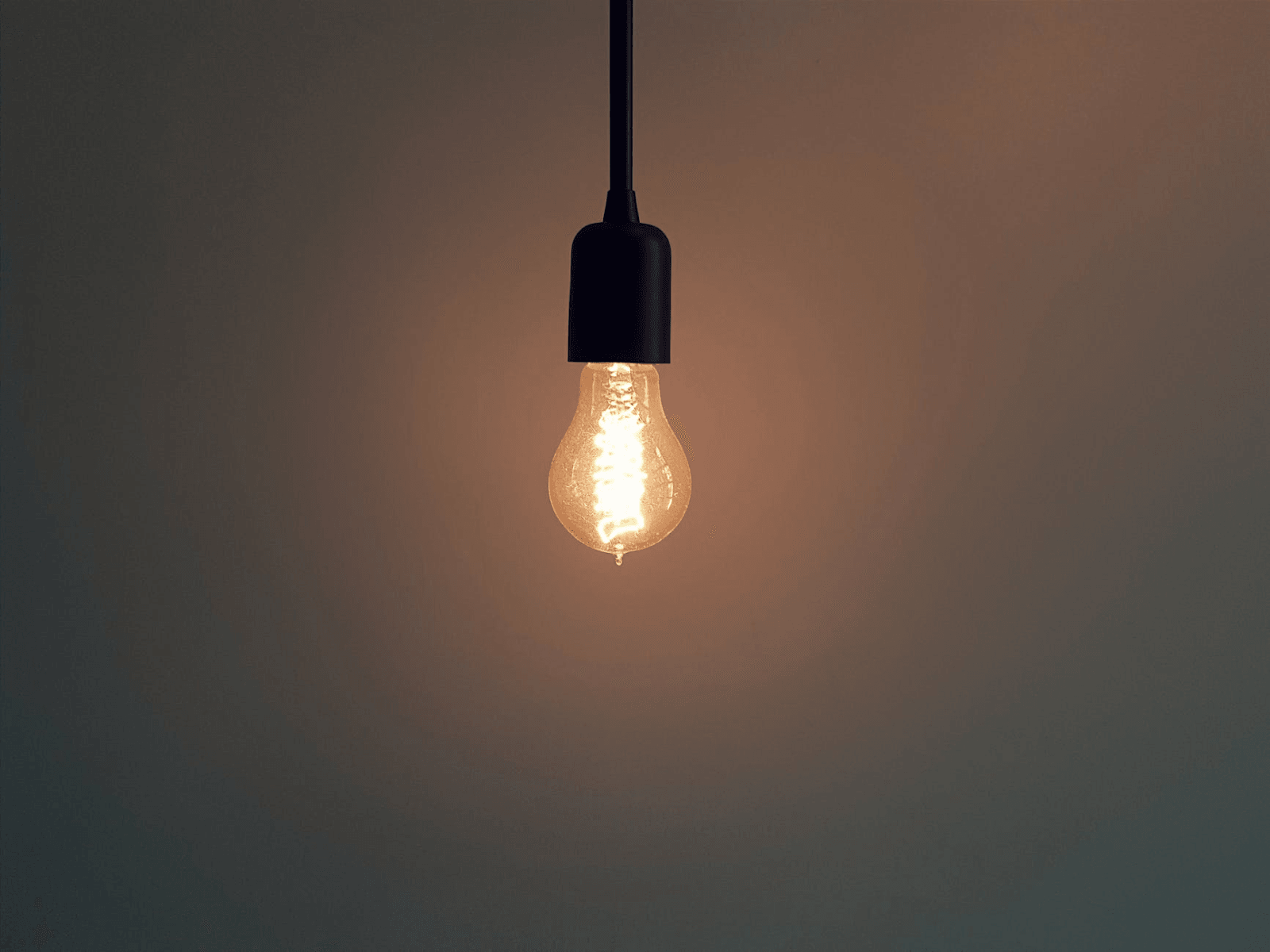 A single lit light bulb hanging from a cord.