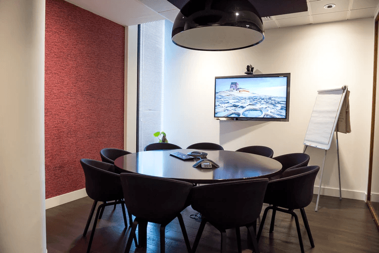 A video conference room complete with table, chairs, and TV screen.