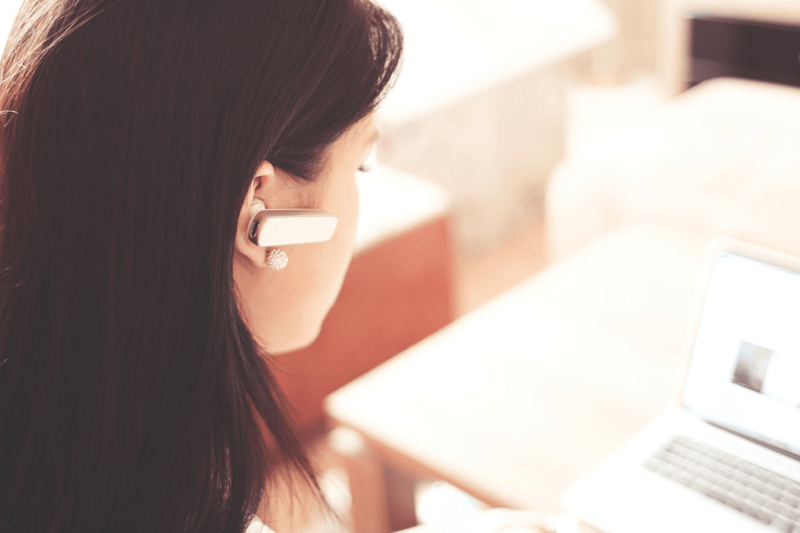 A woman with an earpiece in her ear, working at a computer.
