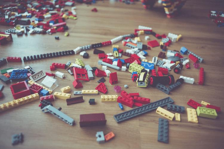 An assortment of Lego blocks on a wood floor.