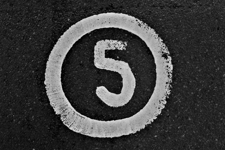 The number 5 painted on asphalt.