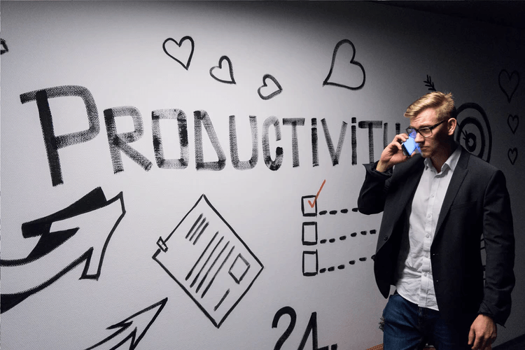 """Man standing in front of a white wall that says """"Productivity""""."""