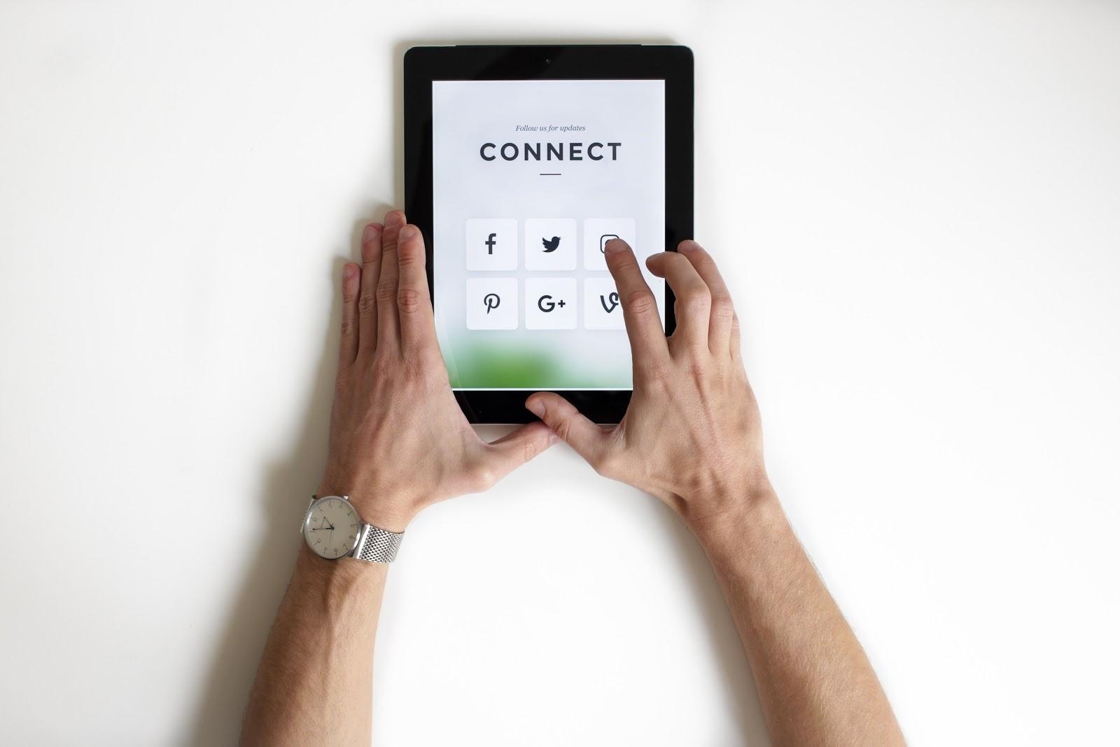 "hands holding ipad with ""connect"" on screen"