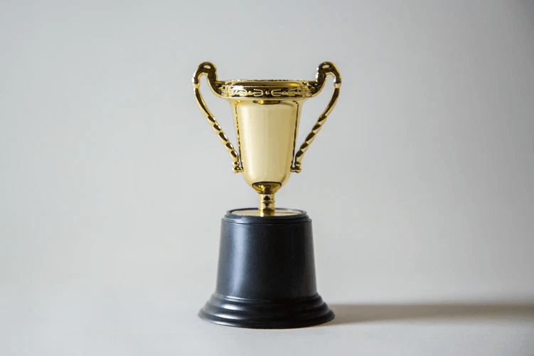 Image of a gold trophy with a black base, sitting against a white background.