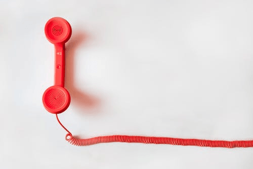 A red phone set against a white background.