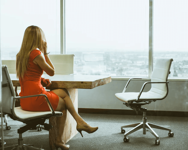 A woman talking on the phone inside a conference room.