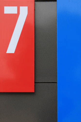 The number seven against a red, black, and blue background.