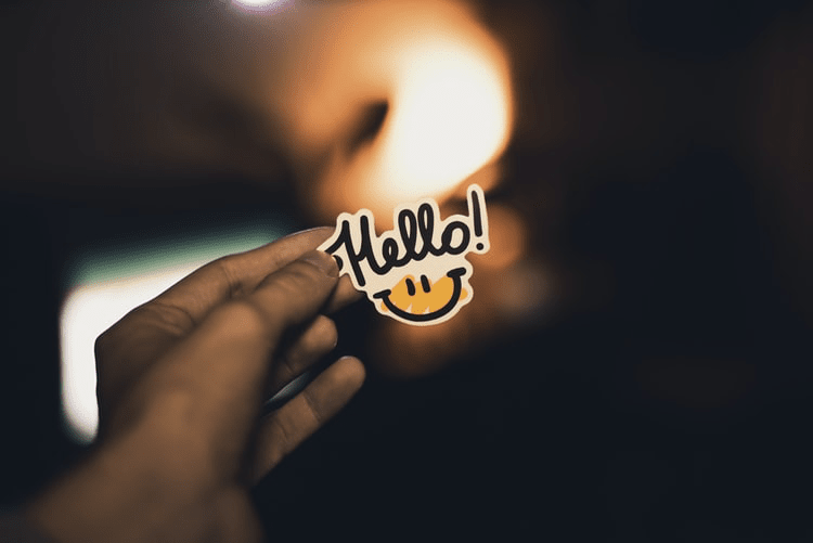 """A hand holding a sticker that says """"Hello!"""""""