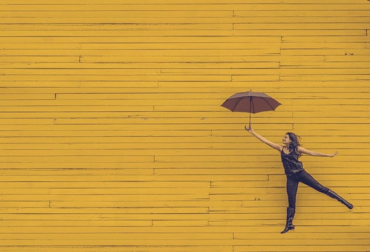 A woman jumping with an umbrella.