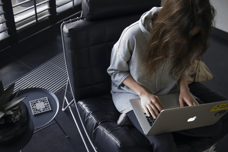 Woman working remotely on a laptop computer.