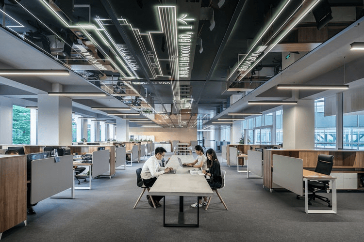 3 people working inside a large office.