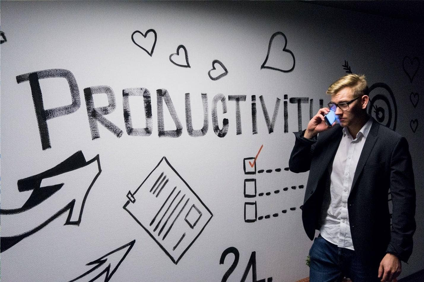 Man walks by productivity written on the wall