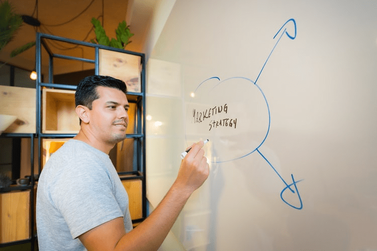 A man writing his go-to-market strategy on a whiteboard.