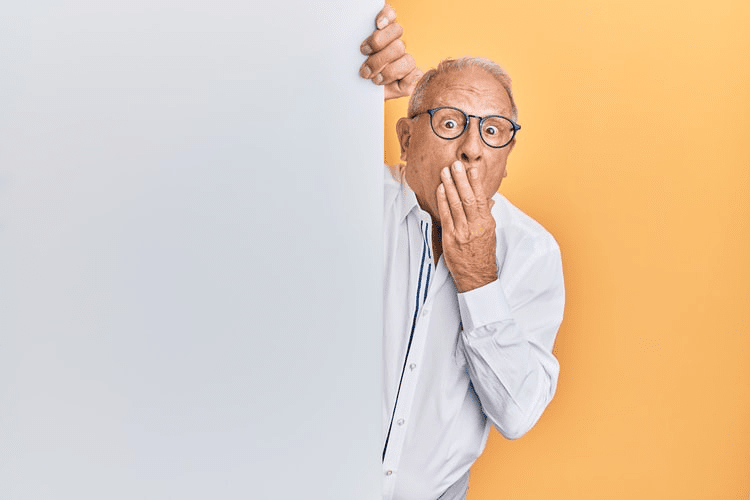 An elderly man holding his hand to his mouth.
