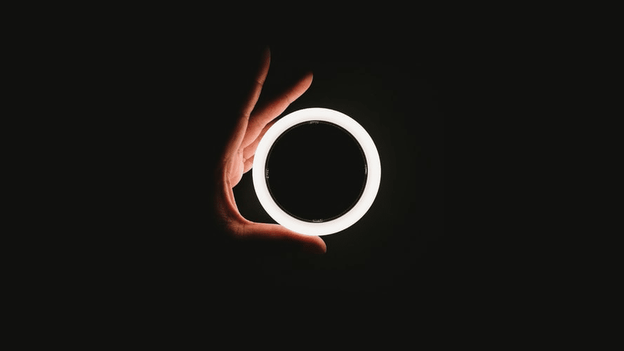 A hand holding a glowing ring.