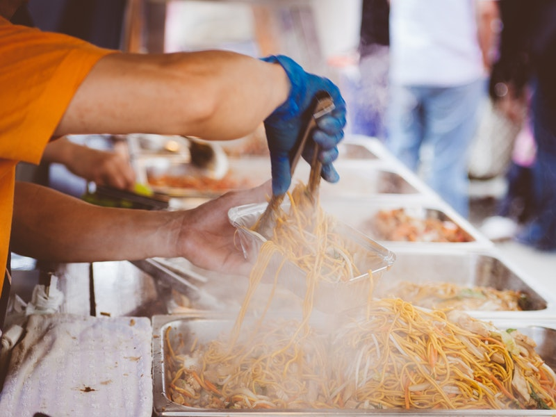 man's arms serving pumpkin french fries at festival