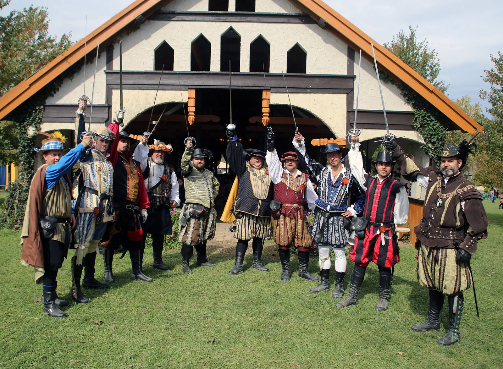 group of men in renaissance costumes holding up swords