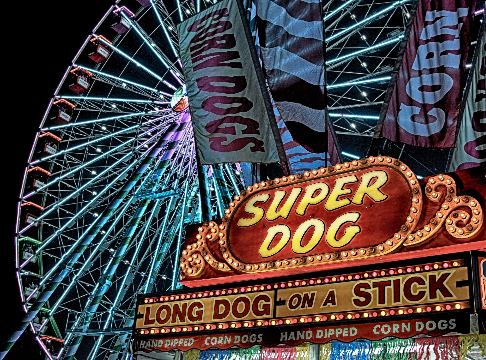 a corn dog stand in front of a ferris wheel