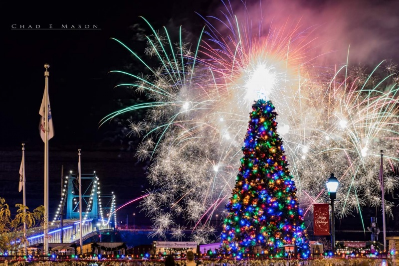large christmas tree with fireworks and lit bridge in the background
