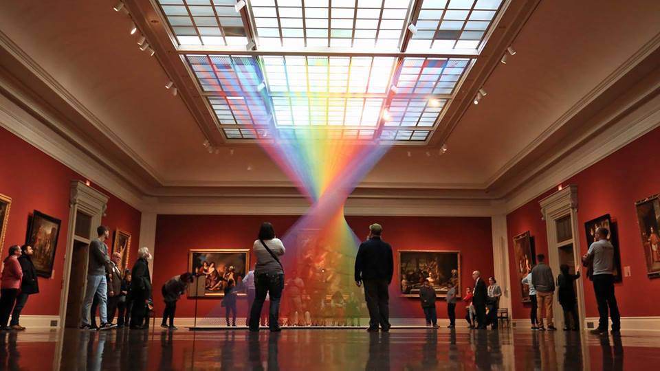 people looking at a rainbow display at the toledo museum of art