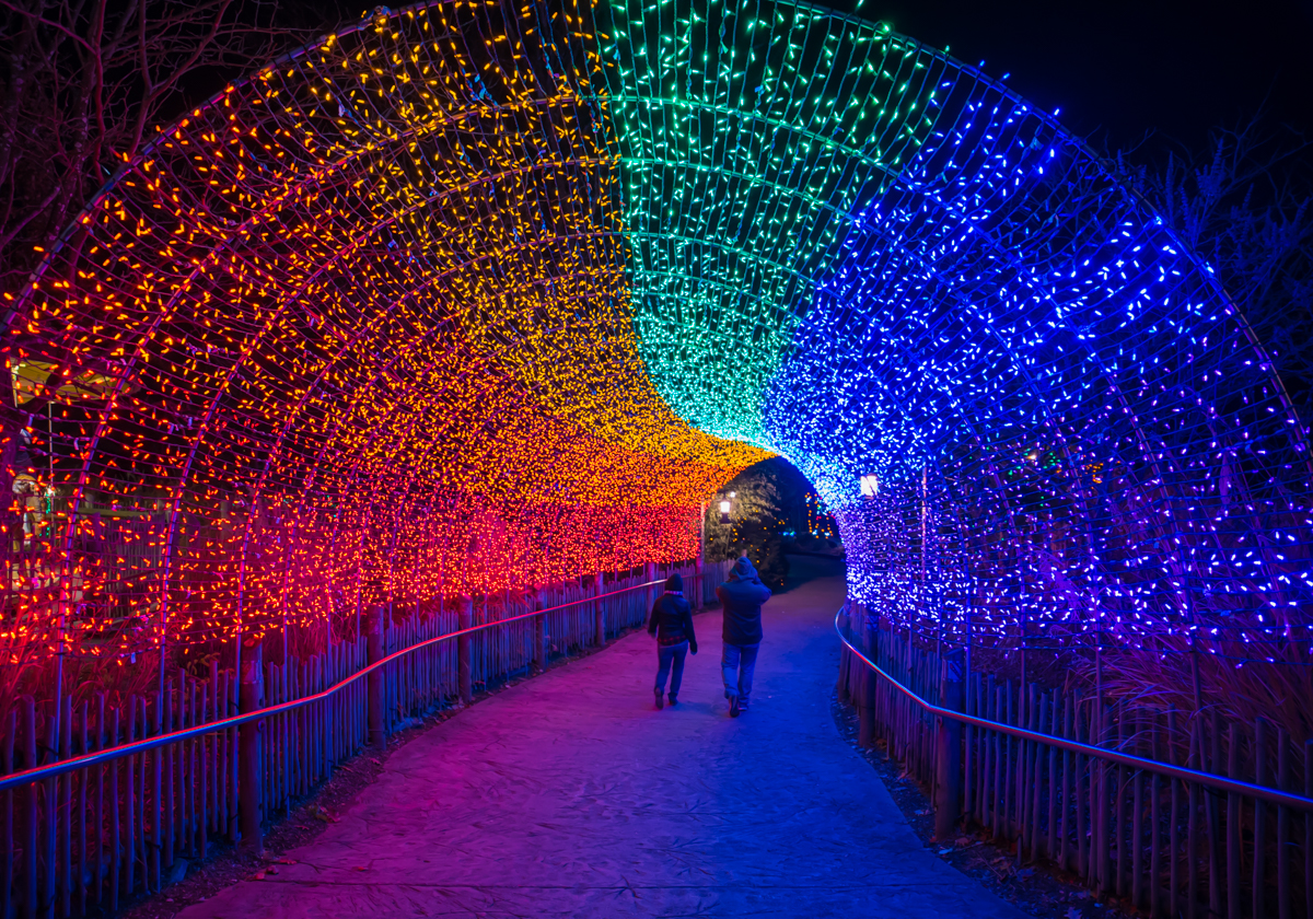 people walking under lit archway at night