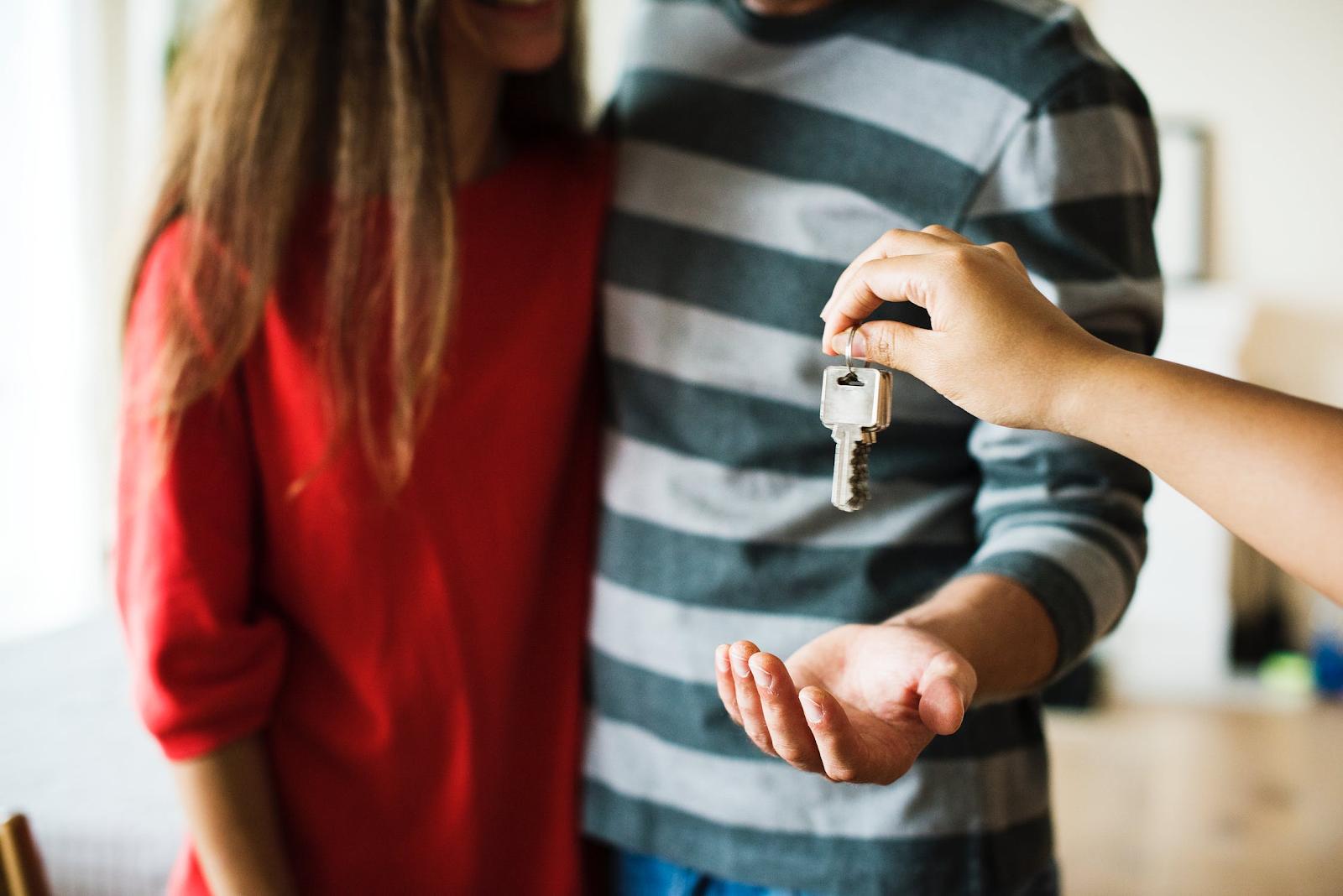 person handing a couple keys