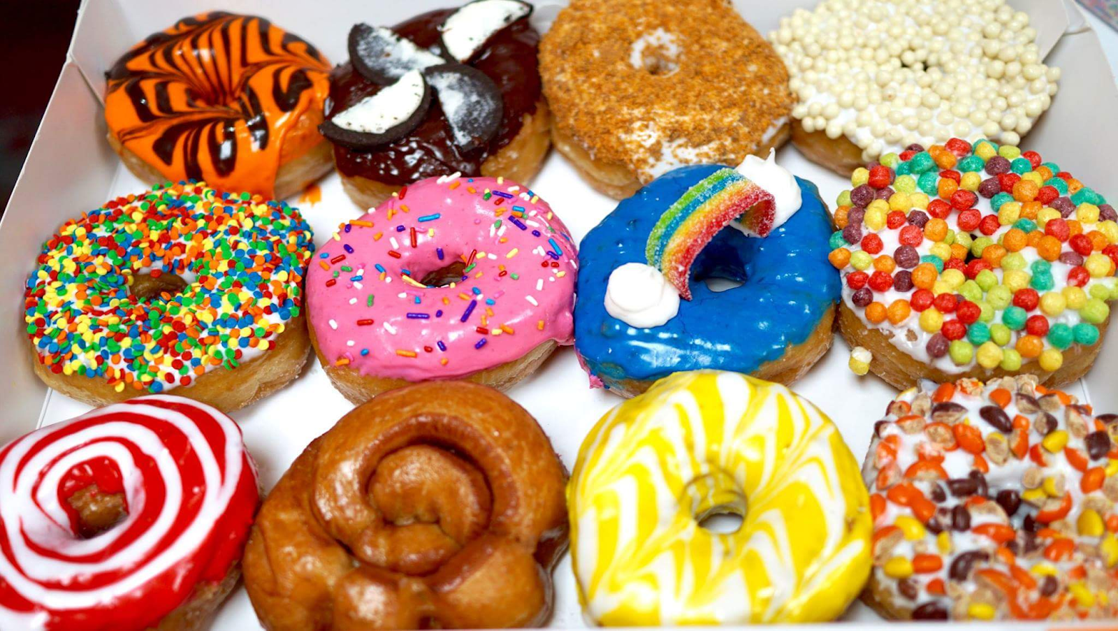 box of a dozen colorfully decorated donuts