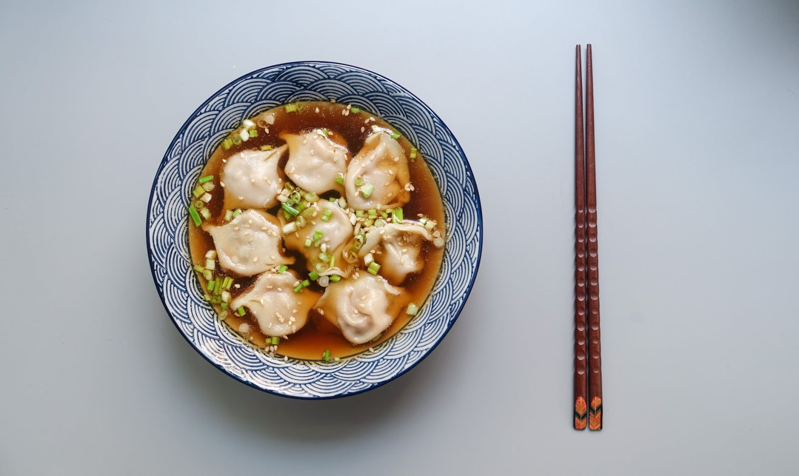 Asian dish on a plate next to chopsticks
