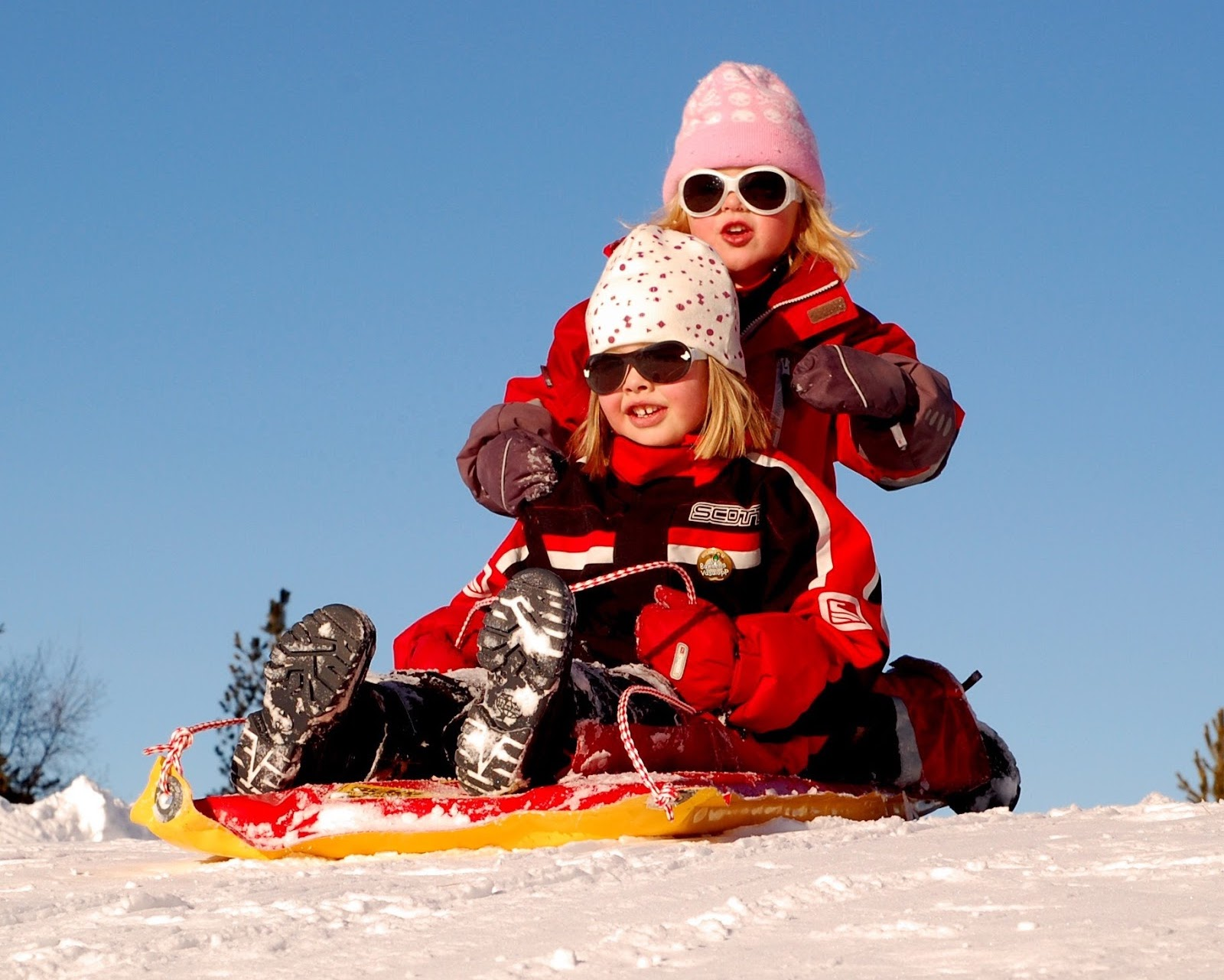 little girls sledding down snowy hill