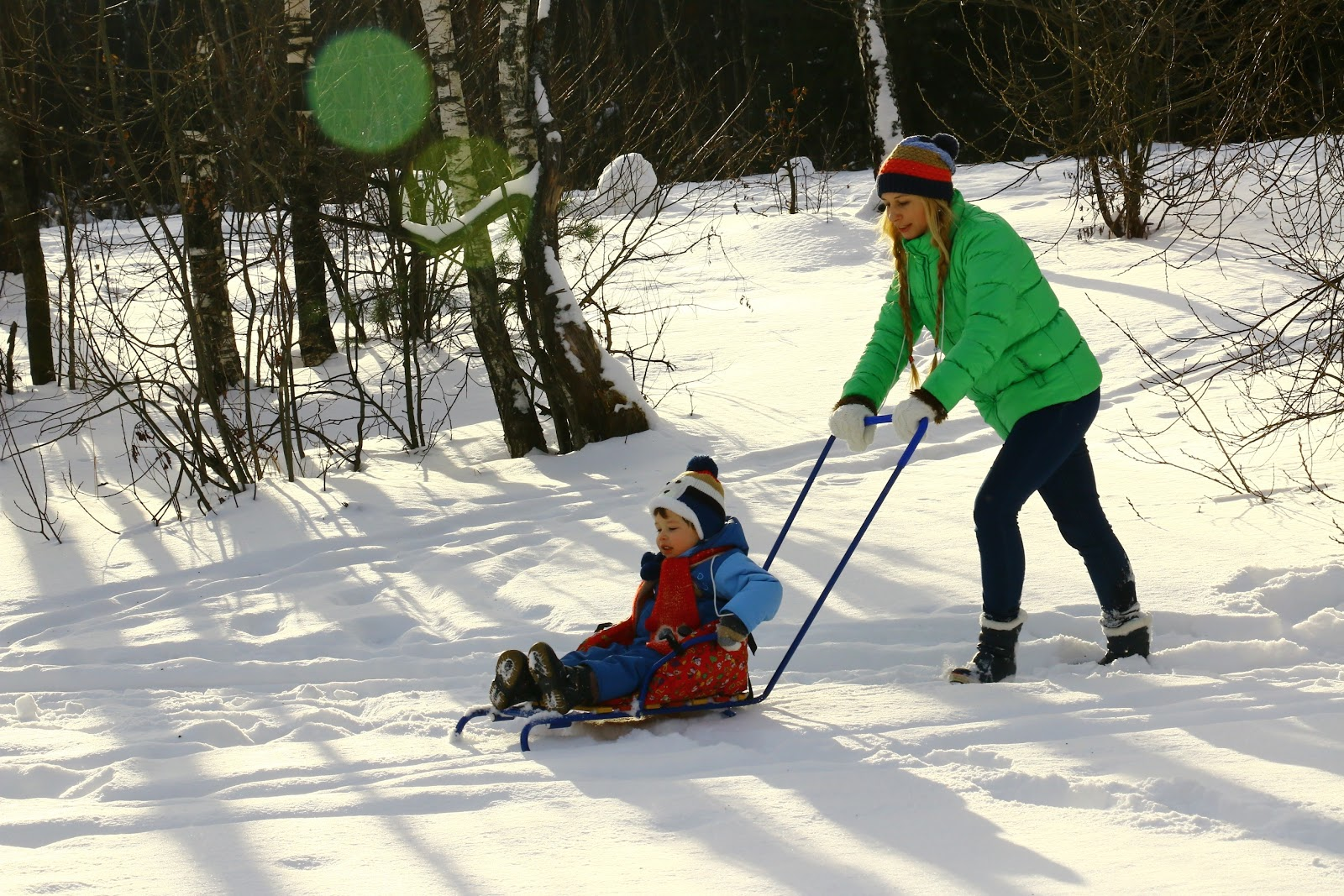 mother pushing child through snow on a sled