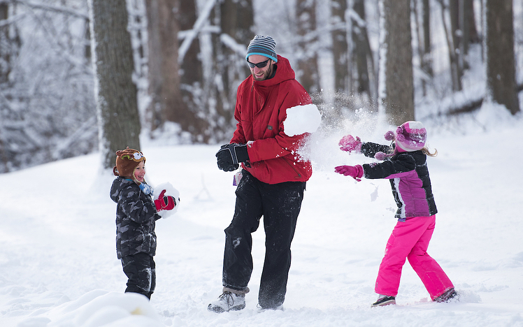 family playing together with snow