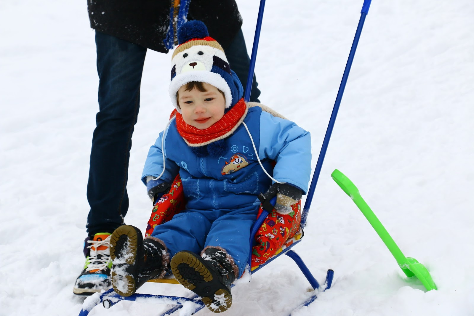 little boy sitting on sled in the snow