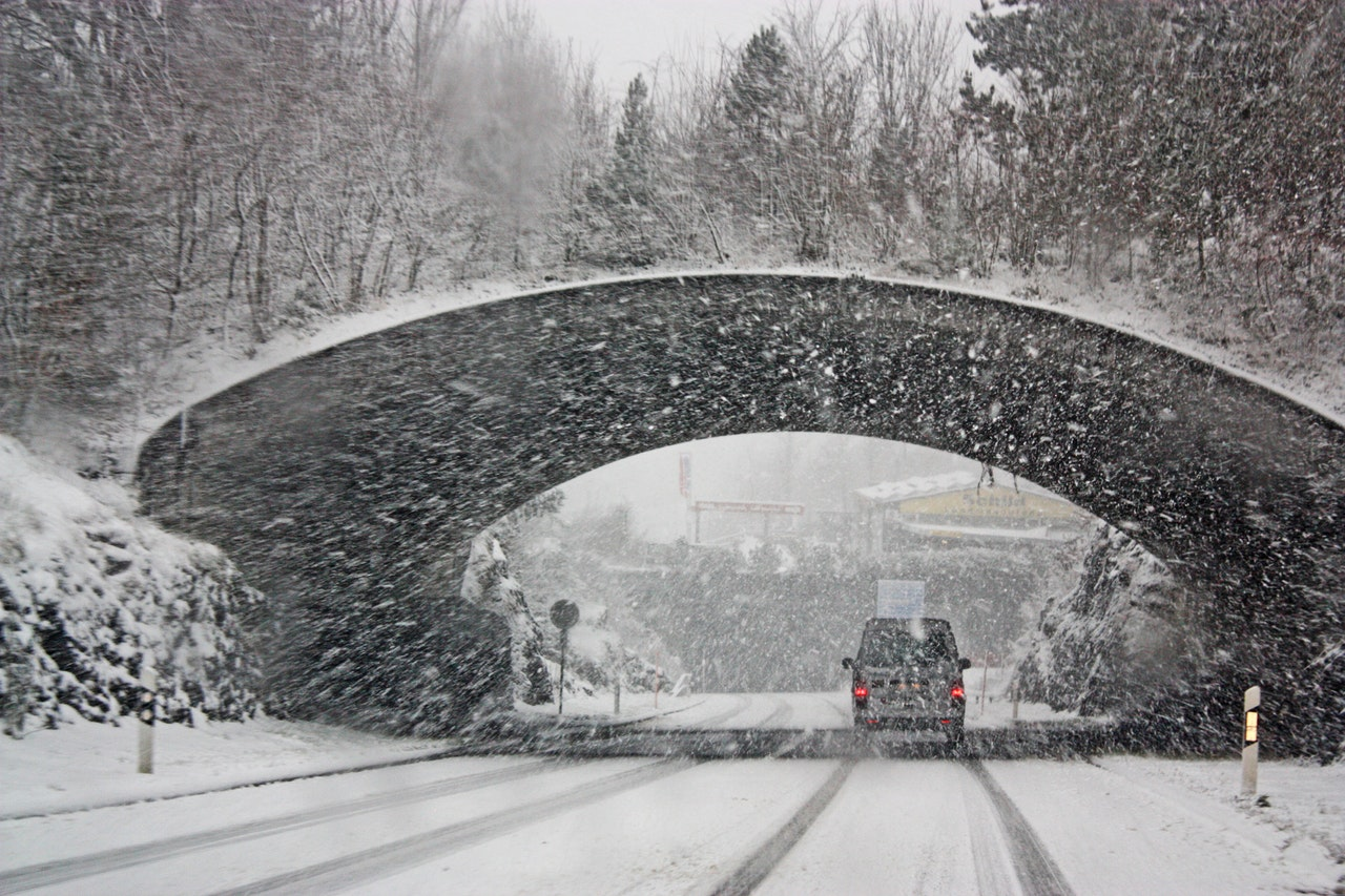a car driving under a tunnel in a blizzard