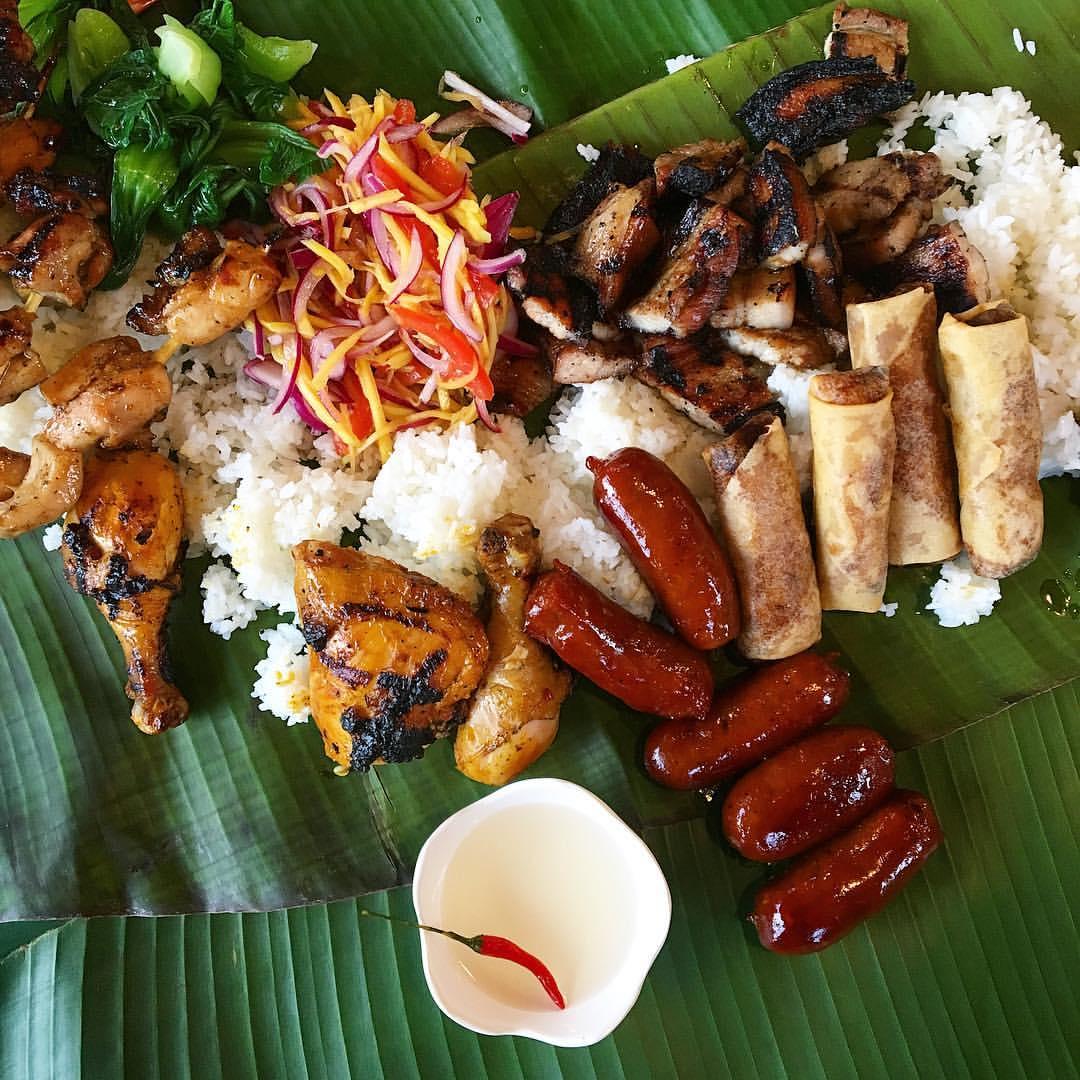 Filipino food spread chicken slaw and banana leaves