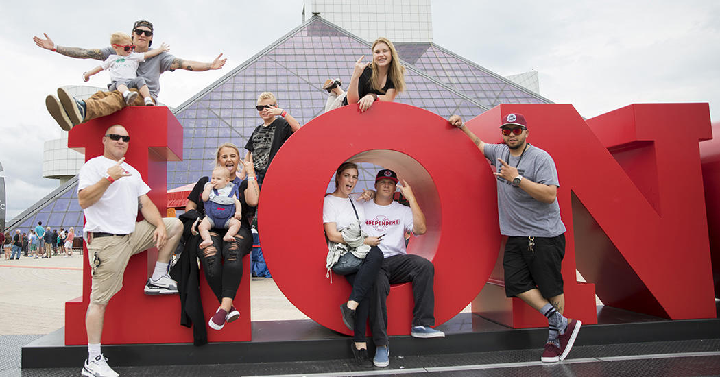 family sitting on large red letters in front of the Rock and Roll Hall of Fame